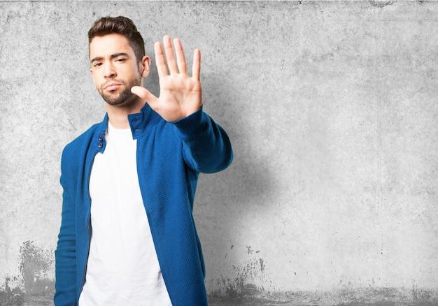 Guy dans un panneau d'arrêt veste de décision bleu Photo gratuit