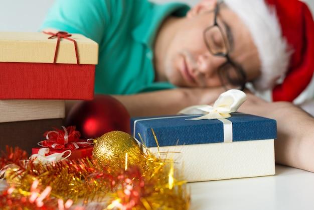 Guy dormant sur la table avec des cadeaux de noël et des boules Photo gratuit