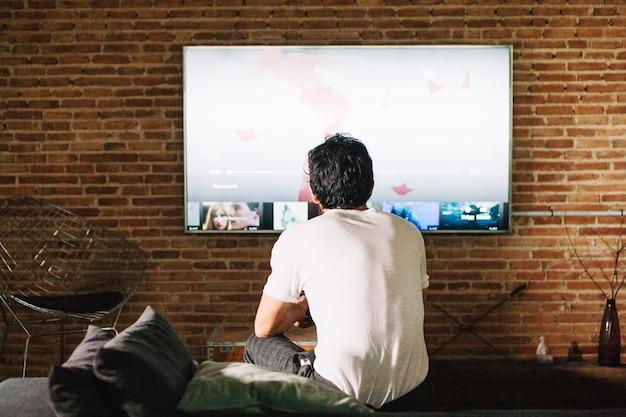 Guy de dos regardant la télévision Photo gratuit