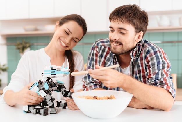 Guy et la fille nourrissent le petit robot rhinocéros. Photo Premium