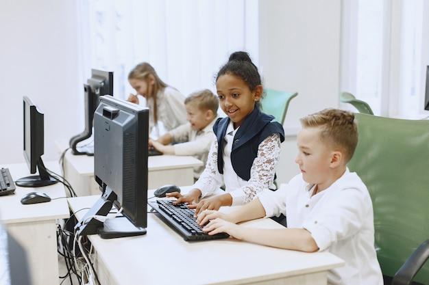 Guy Et La Fille Sont Assis à La Table. Fille Africaine En Classe D'informatique. Les Enfants Jouent à Des Jeux Informatiques. Photo gratuit