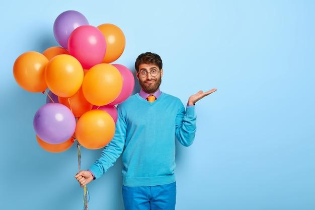 Guy Hésitant Confus Avec Des Ballons Posant En Pull Bleu Photo gratuit