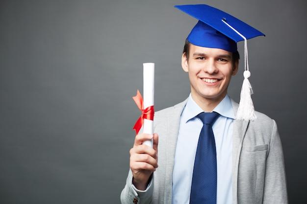 Guy joyful avec son diplôme Photo gratuit