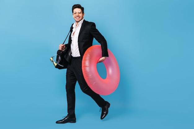 Guy à Lunettes Tient Un Sac Pour Ordinateur Portable. L'homme En Costume Veut Partir En Vacances Et Pose Avec Un Masque De Plongée Et Un Cercle Gonflable Rose. Photo gratuit
