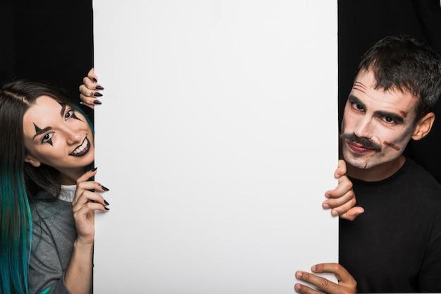 Guy avec moustache et fille aux cheveux d'azur tenant grand drap blanc Photo gratuit