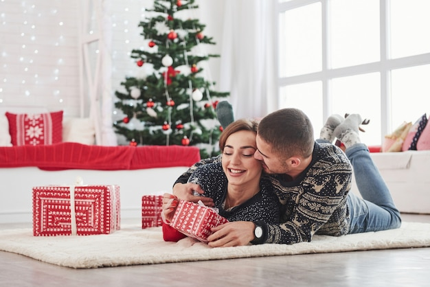 Guy offre à sa femme un cadeau de noël. belle jeune couple allongé sur le salon avec arbre de vacances vert à l'arrière-plan Photo Premium