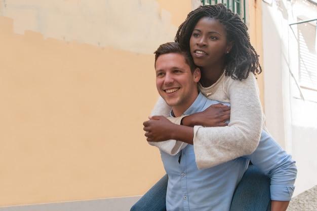 Guy portant une petite amie noire sur le dos en ville Photo gratuit