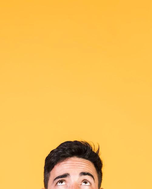 Guy regardant ci-dessus avec espace copie Photo gratuit