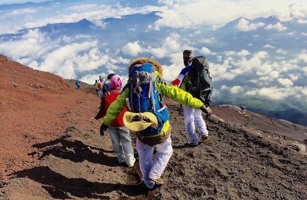 Guy avec un sac à dos de voyage sur le haut d'un rocher Photo Premium
