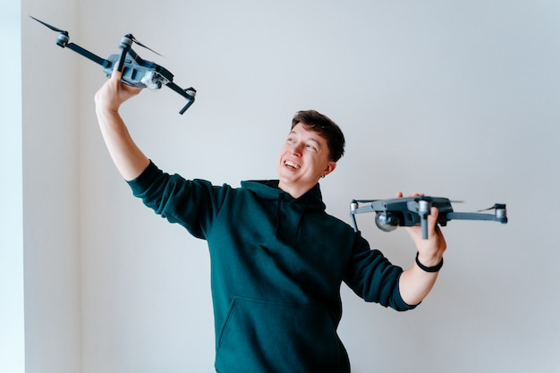 Guy Tient Deux Quadrocoptères Contre Un Mur Photo gratuit