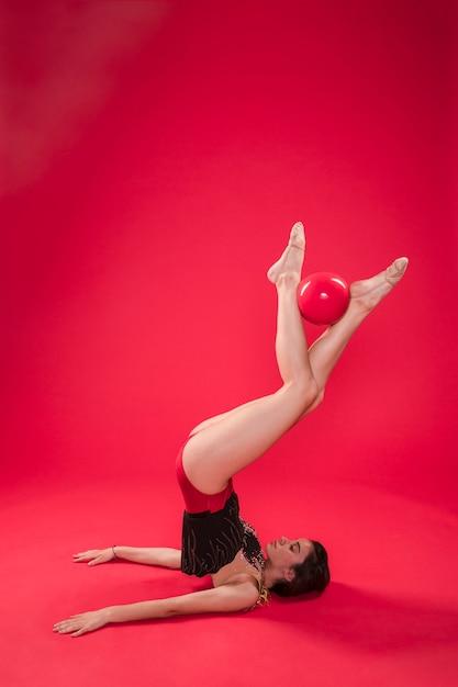 Gymnaste faisant des positions avec le ballon Photo gratuit