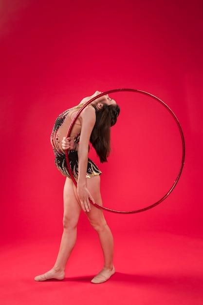 Gymnaste Faisant Des Positions Avec Le Cerceau Photo gratuit