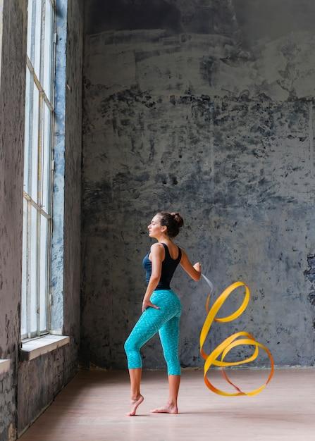 Gymnaste femme dansant avec ruban jaune Photo gratuit