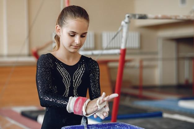 Gymnaste De Fille Dans Les Poignées De Gymnastique étalant La Craie De Gym. Enfant Dans Une école D'athlétisme. Photo gratuit