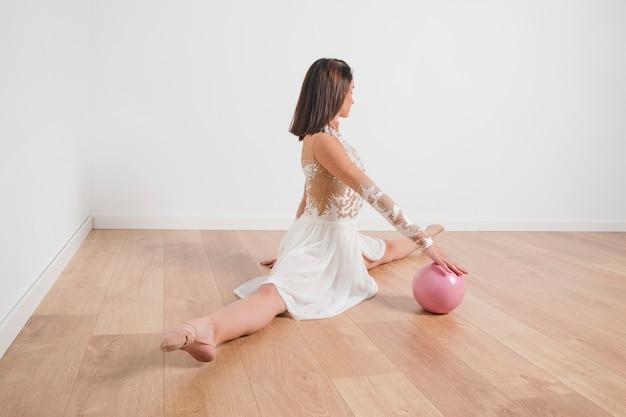Gymnaste rythmique posant avec le ballon Photo gratuit