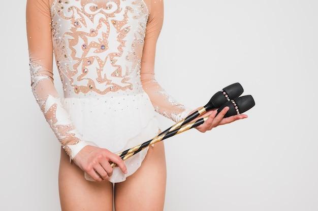 Gymnaste rythmique posant avec les clubs de jonglerie Photo gratuit
