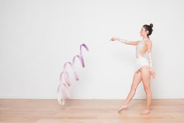Gymnaste rythmique posant avec le ruban Photo gratuit