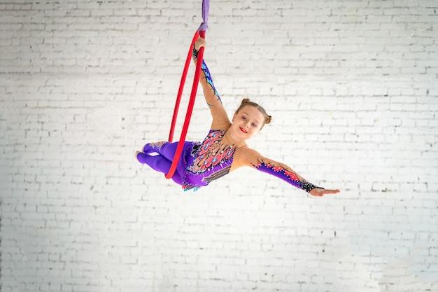 Gymnastique aérienne sur le cercle, une petite fille faisant des exercices Photo Premium