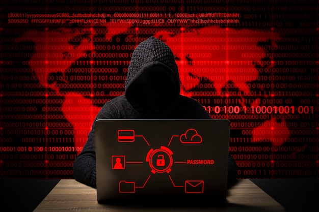 Hacker Dans Une Veste Avec Une Capuche Avec Un Ordinateur Portable Est Assis à La Table Photo Premium