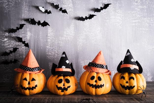 Halloween, citrouilles fantômes orange avec chapeau de sorcière sur une planche en bois grise Photo Premium