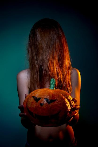 Halloween, Femme En Sous-vêtements Avec Citrouille Dans Ses Mains. Portrait Sur Mur Vert Foncé Photo Premium