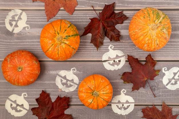 Halloween Fond De Petites Citrouilles Mûres, Feuilles D'érable Tombées Et Pochoir Photo Premium
