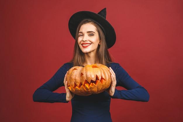 Halloween Sorcière Avec Une Citrouille Sculptée - Isolé Sur Fond Rouge. émotionnelle Jeune Femme En Costume D'halloween. Photo Premium