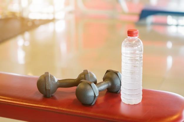 Haltères et bouteille d'eau sur un banc un rouge vide à l'intérieur défocalisé de la salle de sport Photo Premium