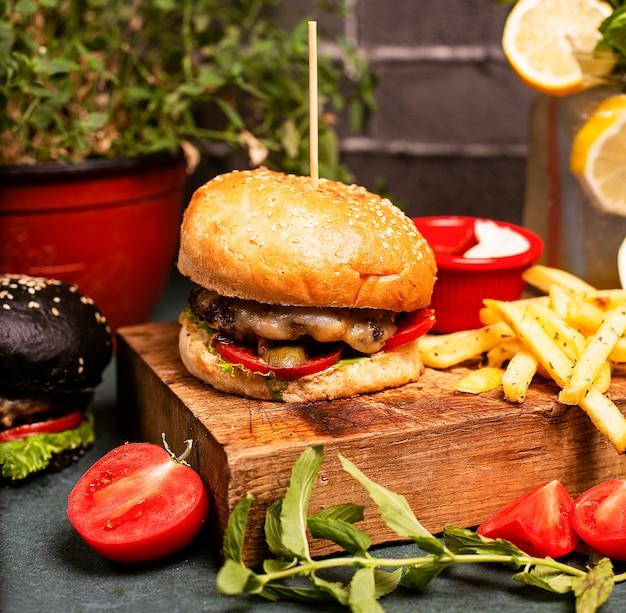 Hamburger au fromage de boeuf avec légumes, fast-food, frites et ketchup Photo gratuit