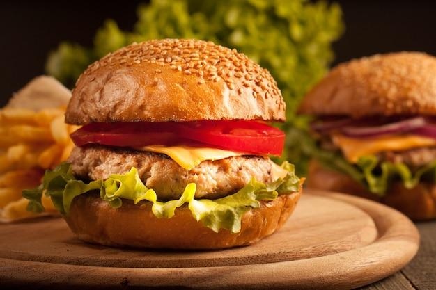 Hamburger fait maison avec du bœuf, de l'oignon, des tomates, de la laitue et du fromage. cheeseburger. Photo Premium