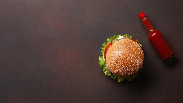 Hamburger fait maison avec du bœuf, des tomates, de la laitue, du fromage, des oignons, des concombres et des frites sur fond rouillé Photo Premium