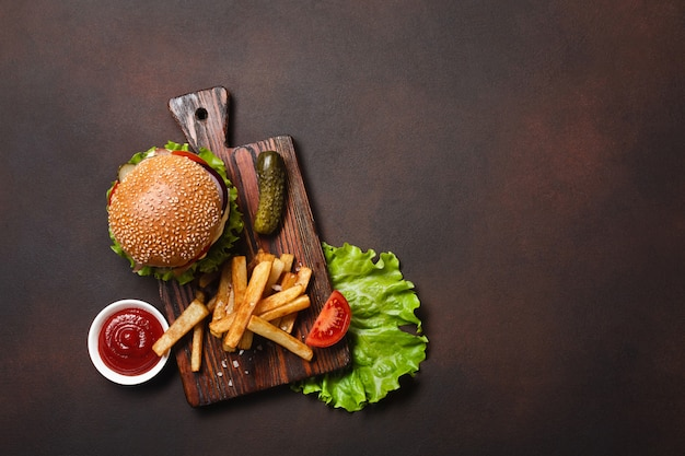 Hamburger fait maison avec du bœuf, des tomates, de la laitue, du fromage, des oignons, des concombres et des frites sur une planche à découper Photo Premium