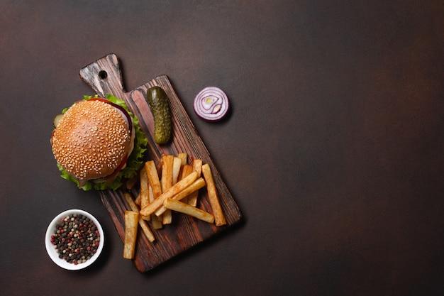 Hamburger fait maison avec du bœuf, des tomates, de la laitue, du fromage, des oignons, des concombres et des frites Photo Premium