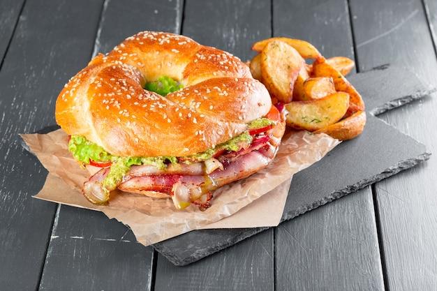 Hamburger avec des frites sur une assiette en ardoise Photo Premium