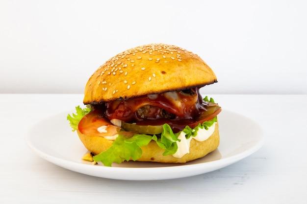Hamburger savoureux chaud sur une assiette sur un fond blanc. hamburger fait maison, farci de galettes de boeuf, de tomates, de concombre et d'oignons marinés, de mayonnaise, de ketchup, de fromage et de salade. fast food Photo Premium