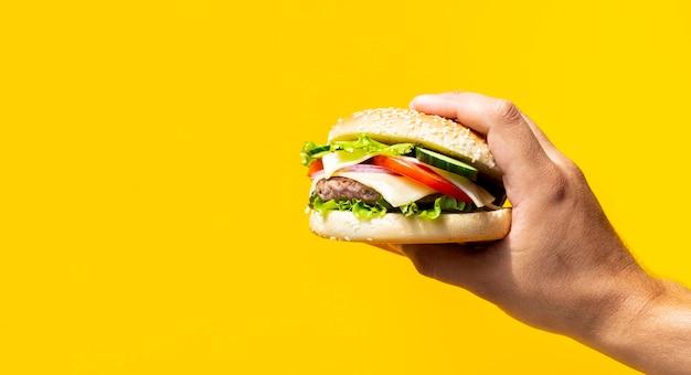 Hamburger tenu devant fond jaune Photo gratuit