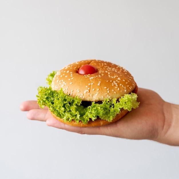 Hamburger vue de face tenu par personne Photo gratuit