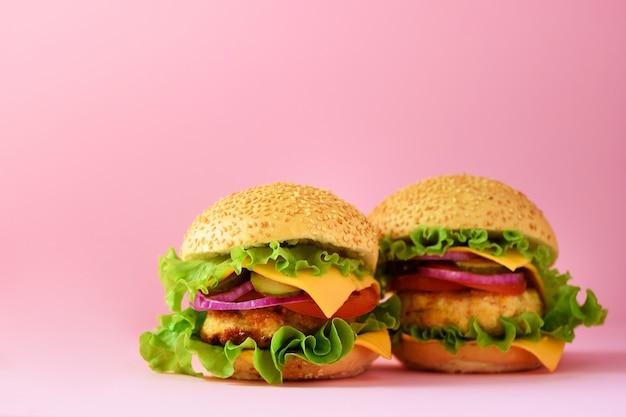 Hamburgers malsains avec boeuf, fromage, laitue, oignon, tomates sur fond rose. repas à emporter. concept de régime malsain et espace de copie Photo Premium