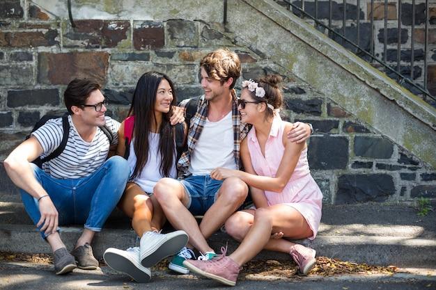 Hanches amis discutant et assis sur le trottoir en ville Photo Premium