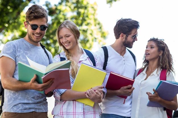Hanches amis lisant des notes sur des cahiers à l'extérieur Photo Premium