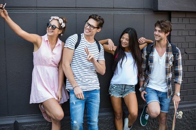 Hanches amis prenant selfie dans la ville, appuyé contre le mur Photo Premium
