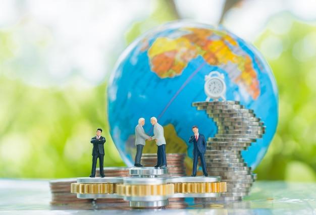 Handshaking homme d'affaires miniature avec globe et piles de plus en plus de fond de pièces de monnaie. Photo Premium