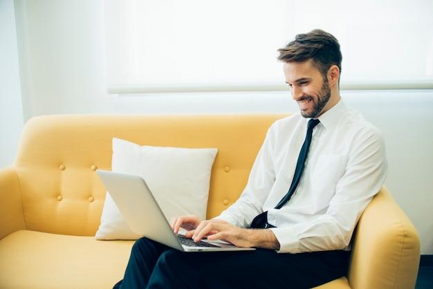 Handsome d'affaires en riant et en travaillant avec son ordinateur portable Photo gratuit