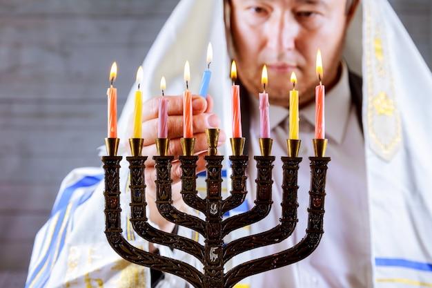 Hanoukka, une fête juive. bougies allumées dans la menorah, homme à l'arrière-plan. Photo Premium