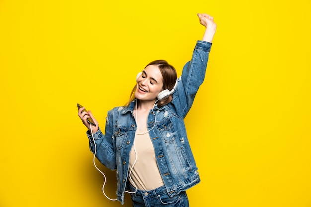 Happy Cheerful Woman Wearing Headphones écouter De La Musique De Smartphone Studio Tourné Isolé Sur Mur Jaune Photo gratuit