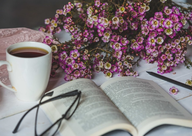Happy corner, fleurs naturelles, tasse de thé, un livre et des lunettes Photo gratuit