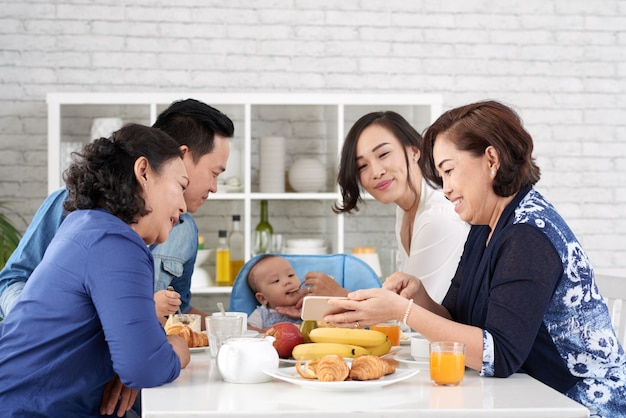 Happy family asiatique à la table du petit déjeuner Photo gratuit