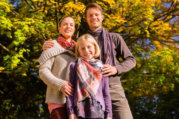 Happy family à l'extérieur assis sur l'herbe en automne Photo Premium