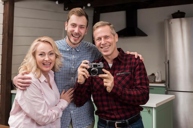 Happy Family Holding Camera Dans La Cuisine Photo gratuit