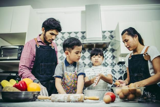 Happy family passe un bon moment à cuisiner ensemble dans la cuisine de la maison. concept de famille Photo gratuit